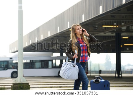 Portrait of a young woman smiling with travel bags and mobile phone