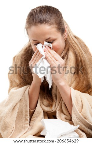 Portrait of a young woman sneezing In to tissue
