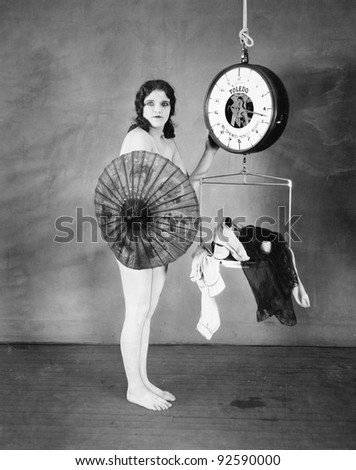 Portrait of a young woman standing in front of a weighing scale and hiding herself with a parasol - stock photo