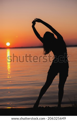 portrait of a Young woman standing on a beach and doing yoga exercises - stock photo