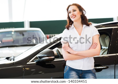 portrait of a young woman stands with his arms crossed over his chest in the cars showroom - stock photo