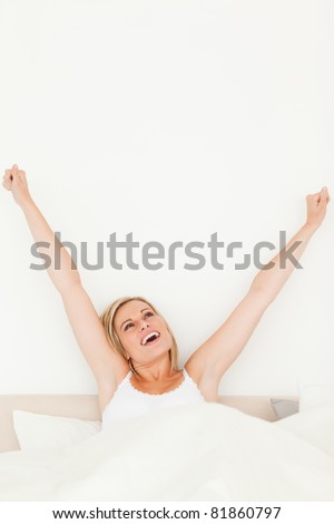 Portrait of a young woman stretching her arms in her bedroom - stock photo