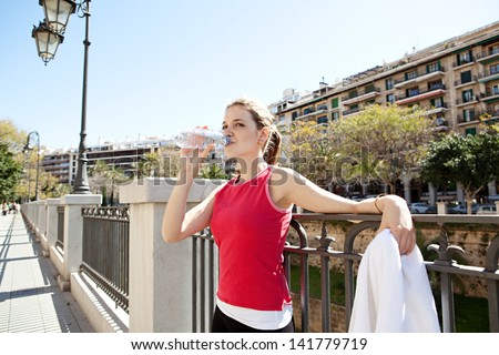 Portrait of a young woman taking a break from exercising in a city, drinking mineral water and leaning on a bridge railings, against a blue sky with buildings. - stock photo