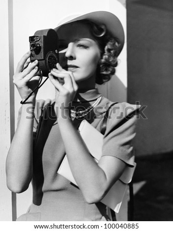 Portrait of a young woman taking a picture with a camera - stock photo