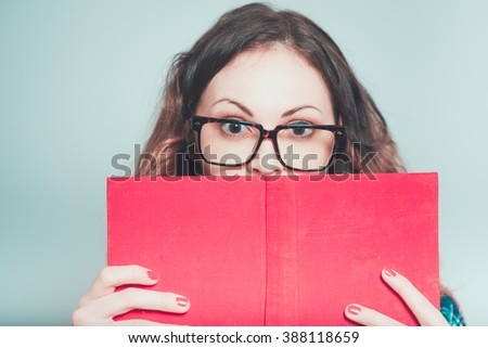 Portrait of a young woman teacher hiding behind the book, isolated on a gray background
