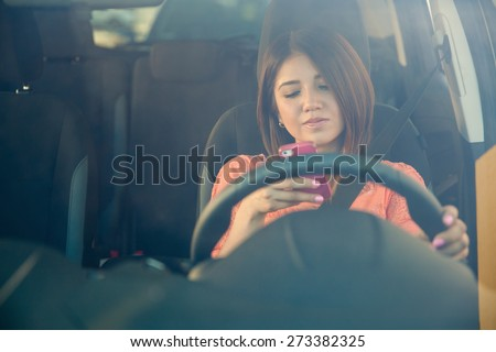 Portrait of a young woman texting on her smartphone while driving a car - stock photo