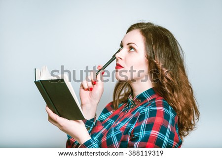 Portrait of a young woman thinking with a notebook and pen, isolated on a gray background - stock photo