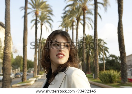Portrait of a young woman turning around in a tree aligned street. - stock photo