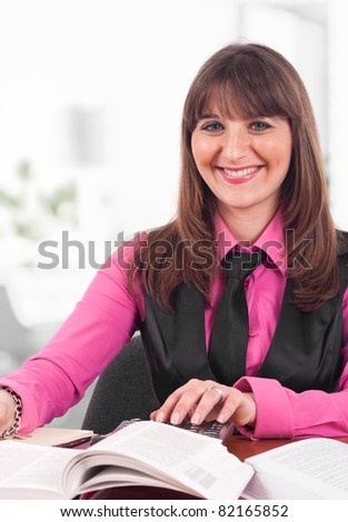 Portrait of a young woman using a calculator - stock photo