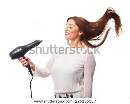 portrait of a young woman using a dryer - stock photo
