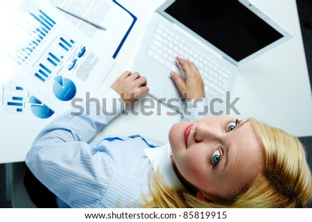 Portrait of a young woman using computer and turning her head to look at the photographer - stock photo