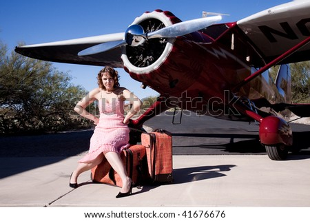 Portrait of a young woman waiting for her flight, annoyed, with a classic 1930's plane.