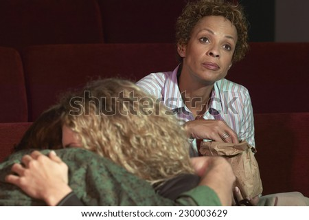 Portrait of a young woman watching a movie from behind a hugging young couple - stock photo