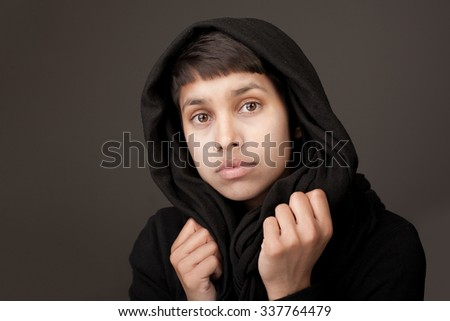 Portrait of a young woman wearing a black afghan scarf - stock photo