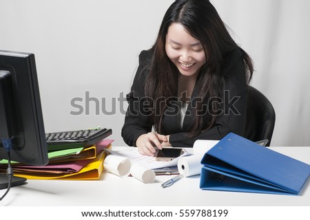 Portrait of a young woman wearing a black suit and playing phone in the office.