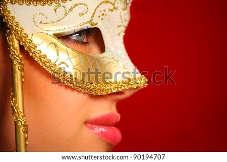 Portrait of a young woman wearing a venetian mask - stock photo