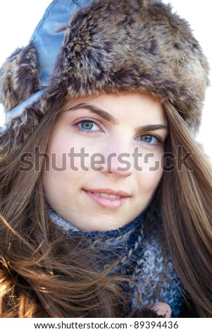 Portrait of a young woman wearing a warm hat in winter. - stock photo