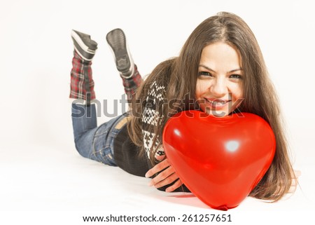 Portrait of a young woman wearing warm winter clothing laying down on the floor smiling, with heart shaped red balloon, Studio portrait on white background - stock photo