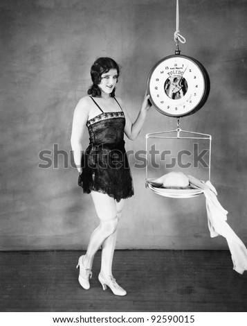 Portrait of a young woman weighing her clothes on a weighing scale - stock photo
