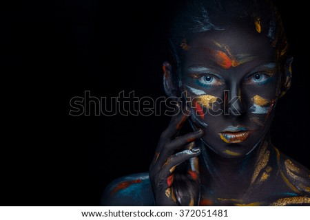 Portrait of a young woman who is posing covered with  black paint  - stock photo