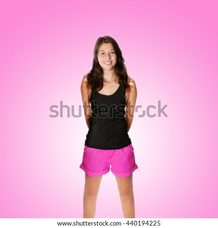 Portrait of a young woman with a beautiful smiling face, she's wearing pink shorts and a black shirt in front of pink background - stock photo