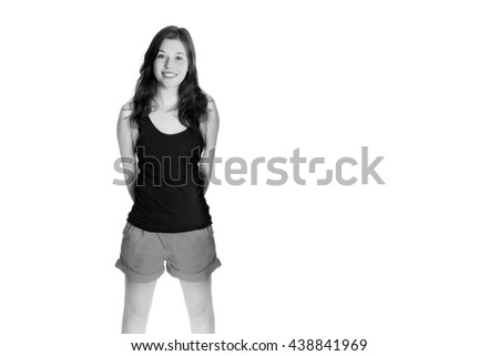 Portrait of a young woman with a beautiful smiling face, she's wearing shorts and black shirt in front of white studio background, black and white photo with copy space on the right side of the image - stock photo