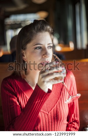 Portrait of a young woman with a glass of white wine.