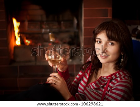 Portrait of a young woman with a glass of wine near the fireplace