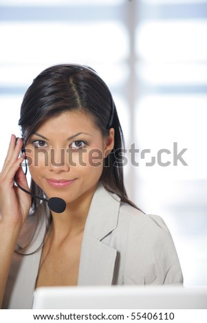 Portrait of a young woman with a headset in front of a laptop computer - stock photo
