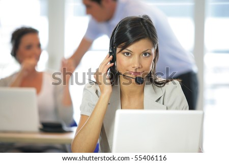 Portrait of a young woman with a headset in front of a laptop computer