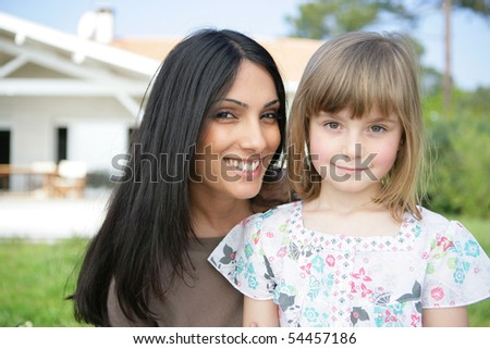 Portrait of a young woman with a little girl - stock photo