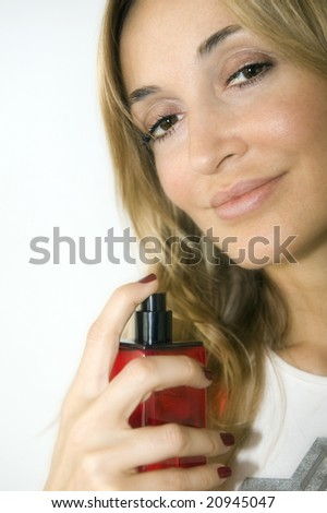 portrait of a young woman with a red perfume bottle - stock photo