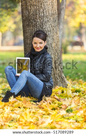 Portrait of a young woman with a tablet sitting in a yellow autumn forest and looking to the camera.