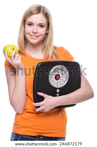Portrait of a young woman with a weight in her hand and an apple. Concept of healthy lifestyle. - stock photo