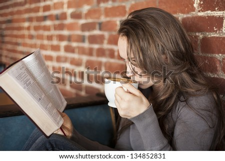 Portrait of a young woman with a white coffee cup reading the book of Mark in the Bible - stock photo