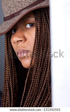 portrait of a young woman with African braids and hat