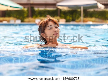 Portrait of a young woman with closed eyes relaxing in a swimming pool
