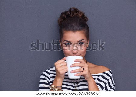 Portrait of a young woman with cup of tea or coffee. - stock photo
