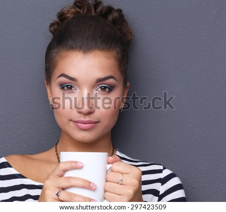 Portrait of a young woman with cup of tea or coffee, isolated - stock photo