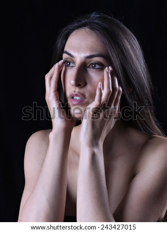 Portrait of a young woman with hands on face