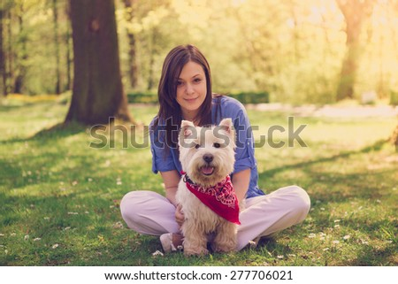 Portrait of a young woman with her dog in the park on a sunny day - stock photo