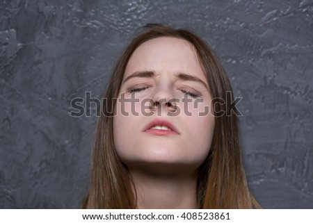 Portrait of a young woman with her eyes closed - stock photo