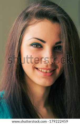 Portrait of a young woman with long hair. Cute little girl looking at the camera and smiling.
