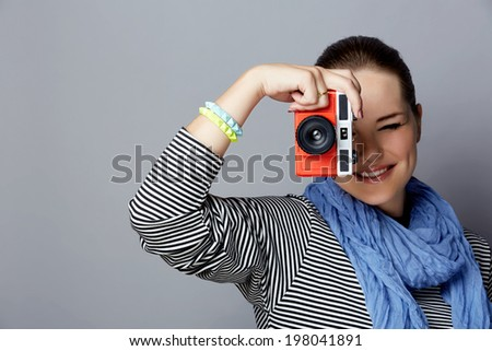 Portrait of a young woman with red retro camera wearing striped top and scarf on grey studio background - stock photo
