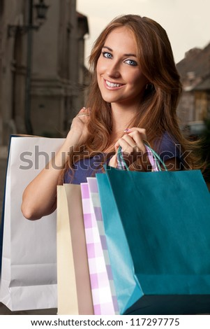 Portrait of a young woman with shopping bags in the arms - stock photo