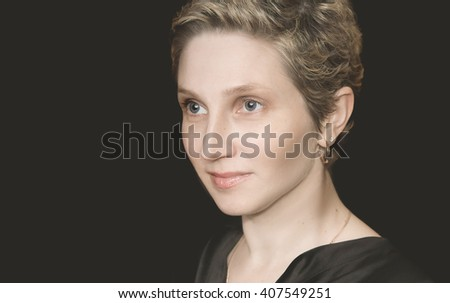 portrait of a young woman with short hair on a black background