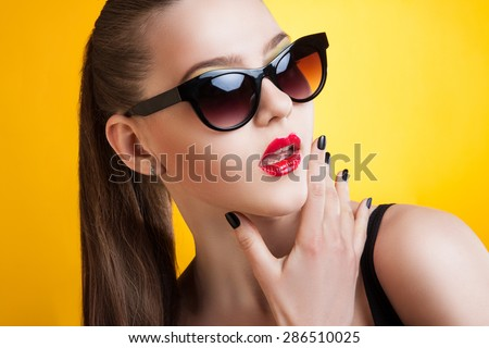 Portrait of a young woman with sunglasses on a yellow background