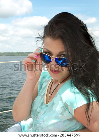 portrait of a young woman with the sunglasses on a background of sky and water - stock photo