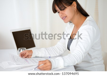 Portrait of a young woman working with documents at office - copyspace