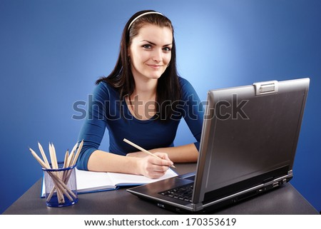 Portrait of a young woman working with laptop on blue background